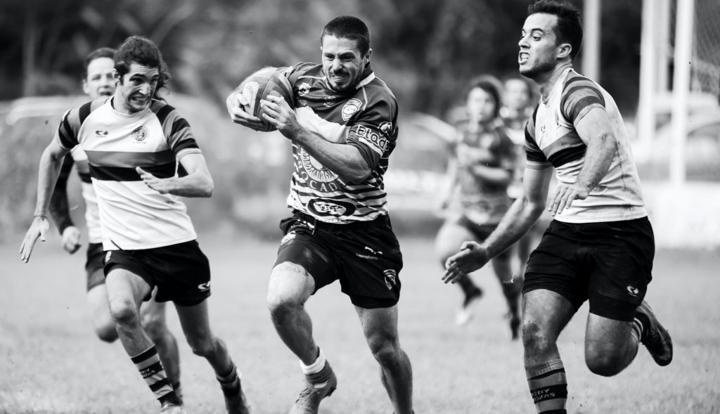 grayscale photography of men playing rugby